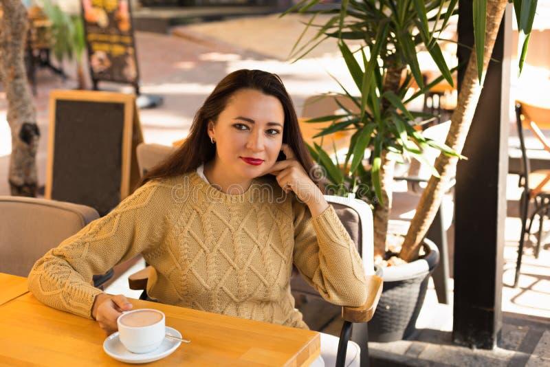 Wijfje die in warme sweater in openluchtkoffie hete chocolade drinken royalty-vrije stock afbeelding