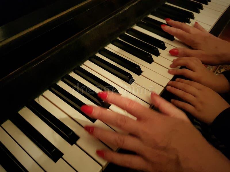 Wijfje en kinderen` s de handen spelen de piano stock fotografie