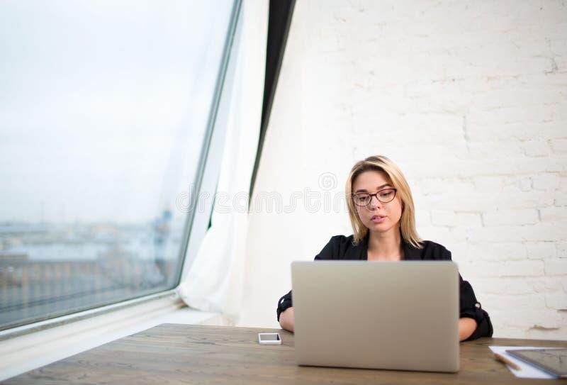 Wijfje in glazen succesvolle tevreden schrijver die draagbaar netto-boek gebruiken stock afbeelding