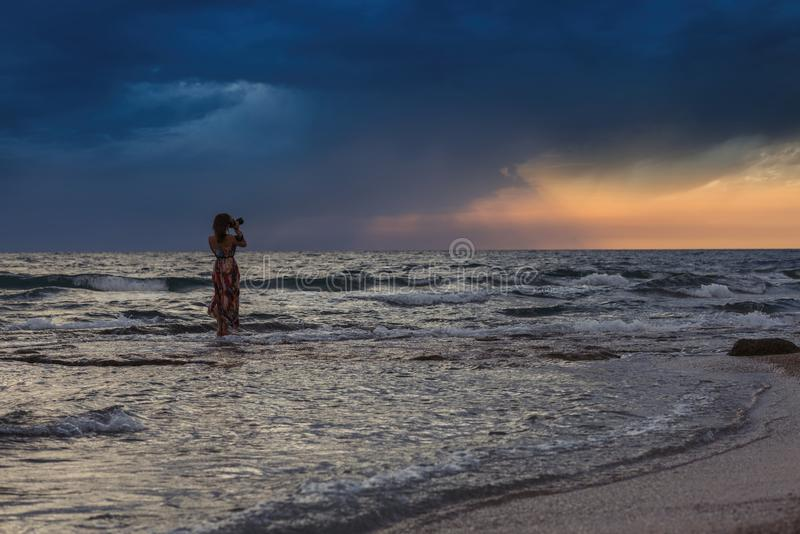 Wijfje met camera in het overzees dichtbij kust van het Griekse eiland in stormachtig weer Het ` s die op de horizon regenen stock foto's