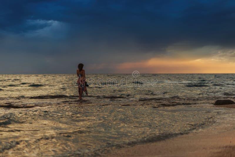 Wijfje met camera in het overzees dichtbij kust van het Griekse eiland in stormachtig weer Het ` s die op de horizon regenen royalty-vrije stock afbeeldingen