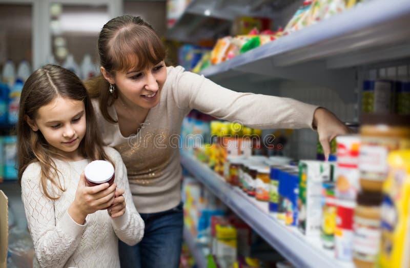 Wijfje met dochter die ingeblikte goederen in voedselopslag kiezen stock foto's