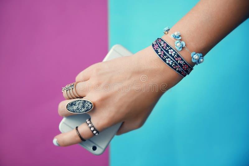 Wijfje met juwelen en cellphone op kleurenachtergrond royalty-vrije stock afbeeldingen
