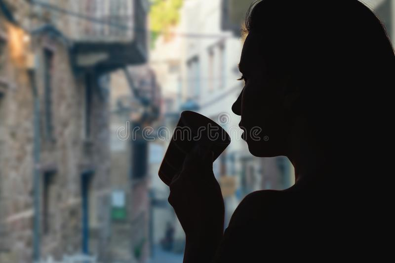 Wijfje met kop thee tegenover smalle straten van de oude stad van Verona Italië stock foto's
