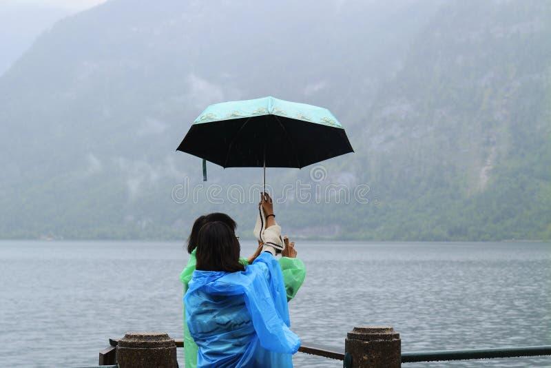 Wijfje twee in blauwe en groene regenjassen met paraplu op de meerkust royalty-vrije stock foto's