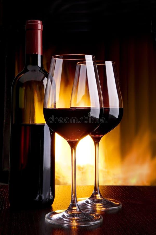 Wijn door het glas tegen de open haard met brand royalty-vrije stock afbeeldingen