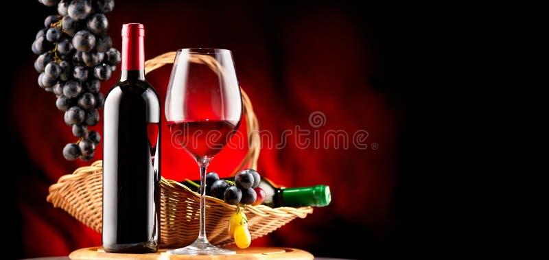 Wijn Fles en glas rode wijn met rijpe druiven stock fotografie