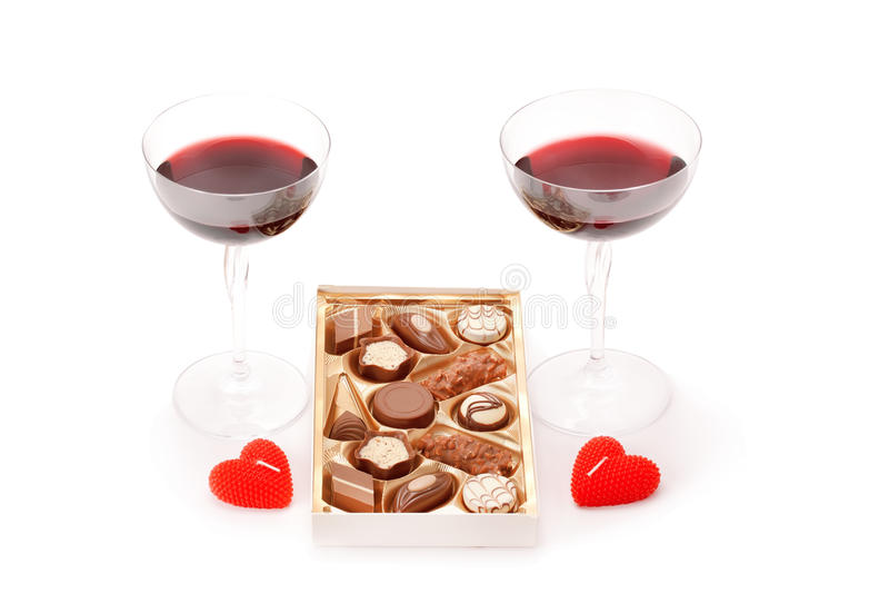 Wijn in glazen en chocoladesuikergoed op wit worden geïsoleerd dat royalty-vrije stock foto's