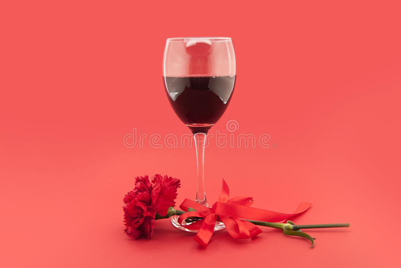 Wijn in glazen, rode anjer met wit lint op rood stock fotografie