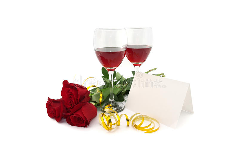 Wijn in glazen, rode rozen, lint en lege kaart voor een bericht, stock afbeelding
