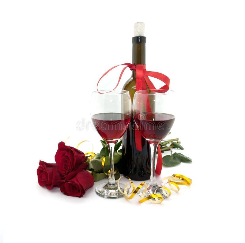 Wijn in glazen, rood die rozen en lint op wit worden geïsoleerd stock afbeeldingen