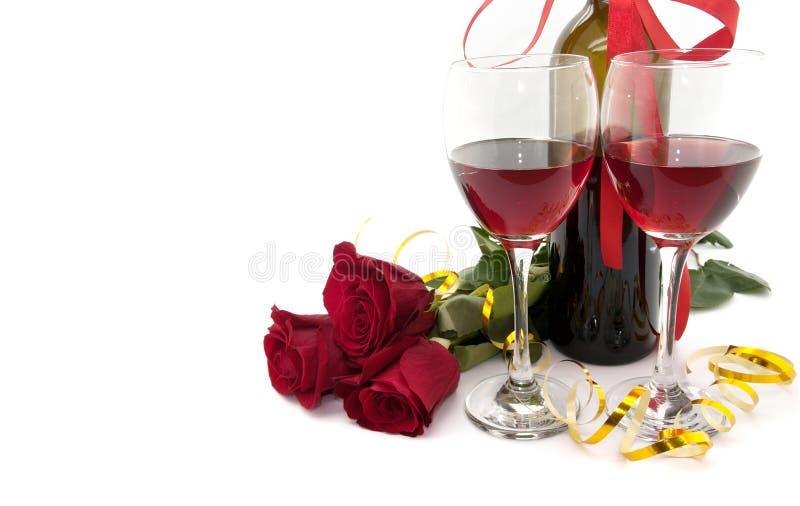 Wijn in glazen, rood die rozen en lint op wit worden geïsoleerd stock foto's
