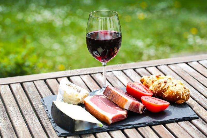 Wijn, kaas en bacon op lei stock afbeelding