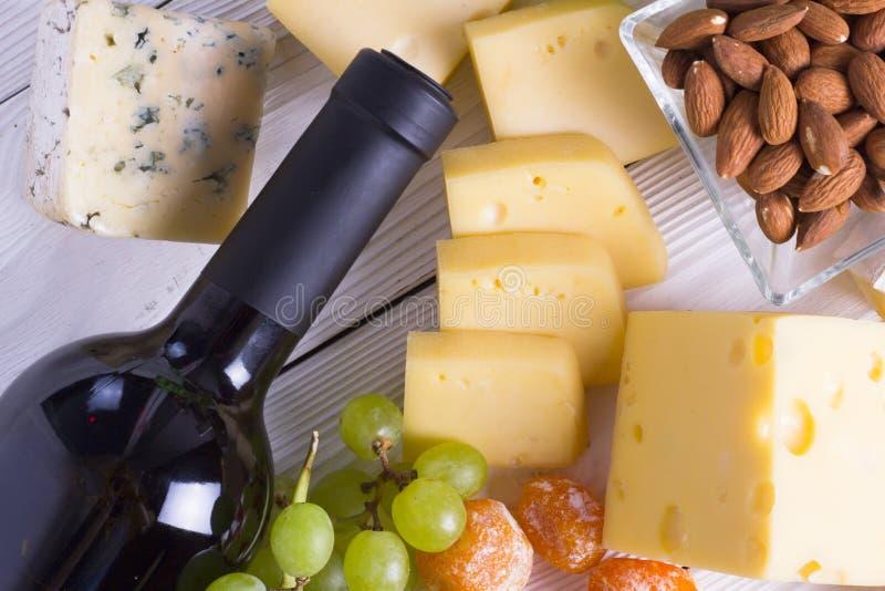 Wijn met snacks - diverse types van kaas, fig., noten, honing, druiven op een houten raadsachtergrond royalty-vrije stock afbeeldingen