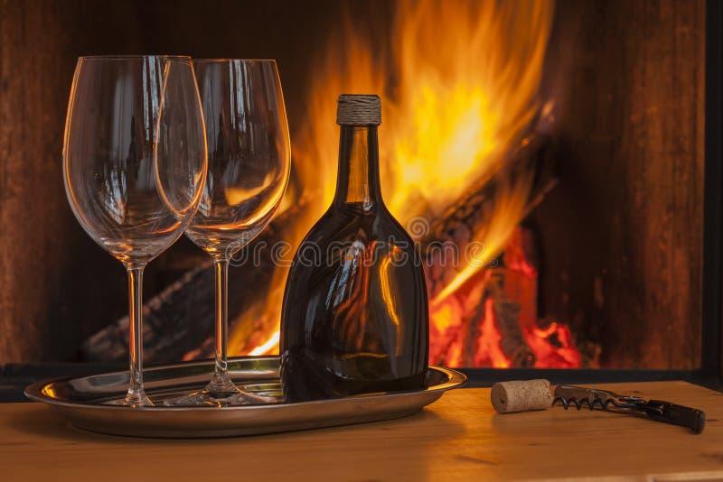 Wijn voor twee bij comfortabele open haard royalty-vrije stock afbeelding