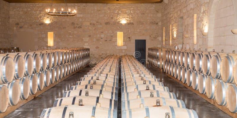 Wijnen die in traditionele grote eiken vaten in de wijnkelder vergisten in het kasteel van Bordeaux stock foto