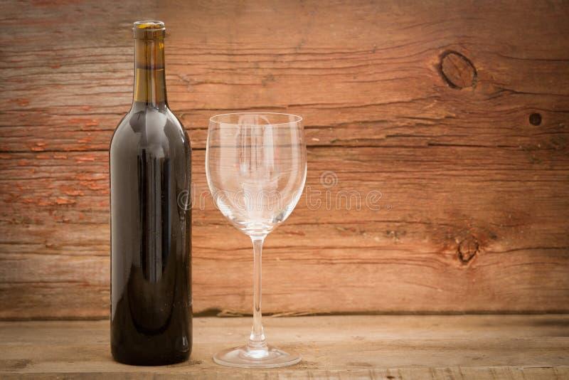 Wijnfles en elegant glas op houten raad stock foto