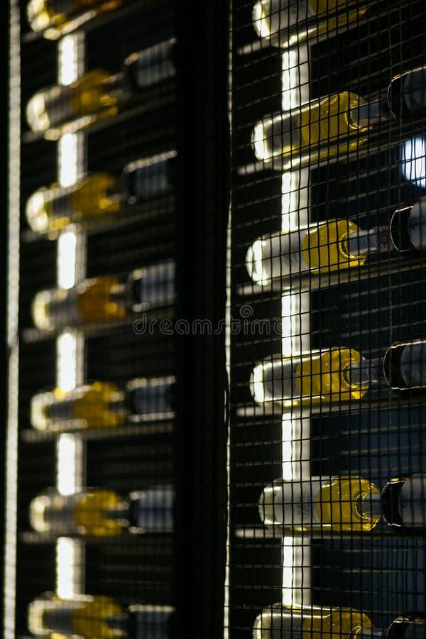 Wijnflessen op een metaalplank stock afbeeldingen