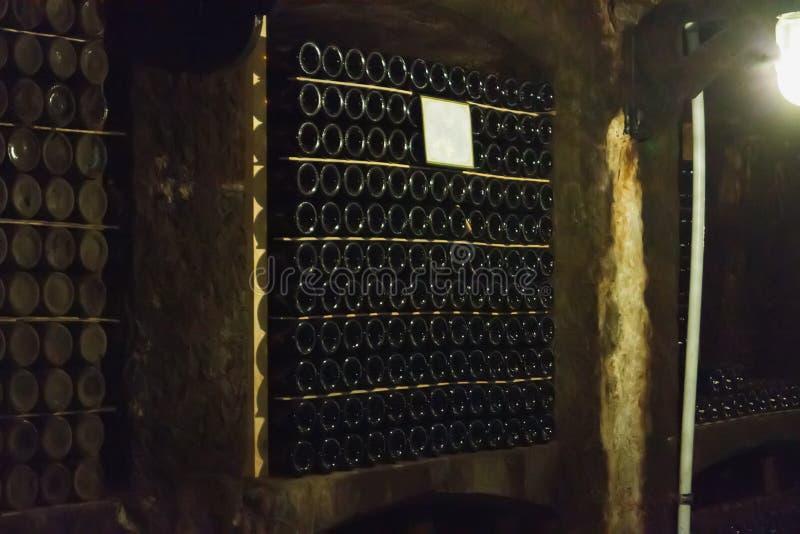 Wijnflessen in rijen worden geschikt die stock afbeelding