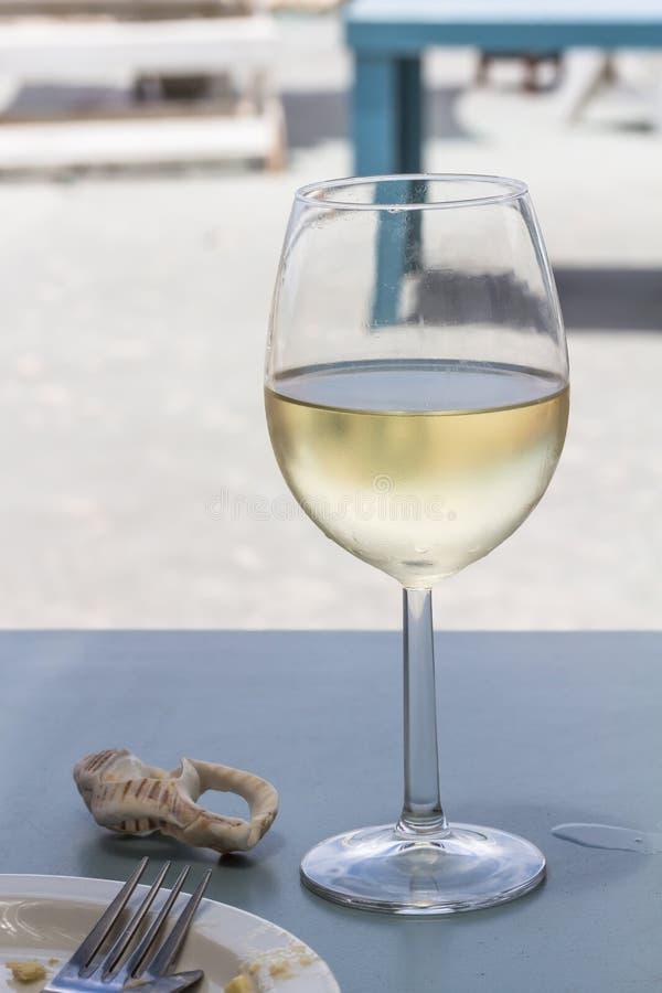 Wijnglas met gekoelde witte wijn bij de lijst van het strandrestaurant in Westkustzuid-afrika stock foto's