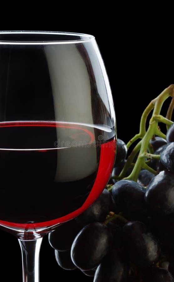 wijnglas met rode wijn en geïsoleerde druiven stock foto's