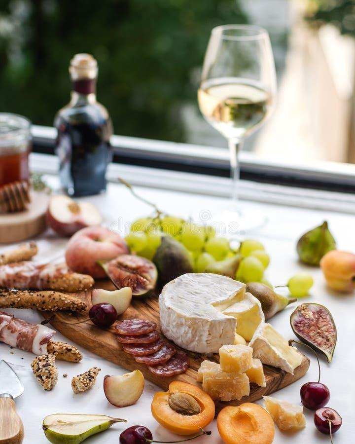 Wijnglas met voorgerecht, camembert, parmezaanse kaaskaas en fruitverscheidenheid stock foto's