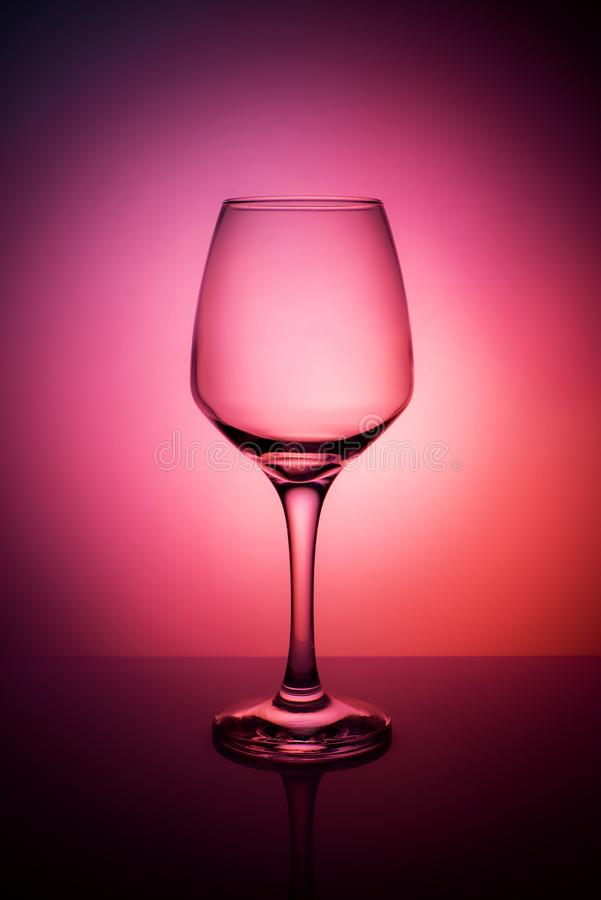 Wijnglas op een purpere rode oranje achtergrond stock afbeelding