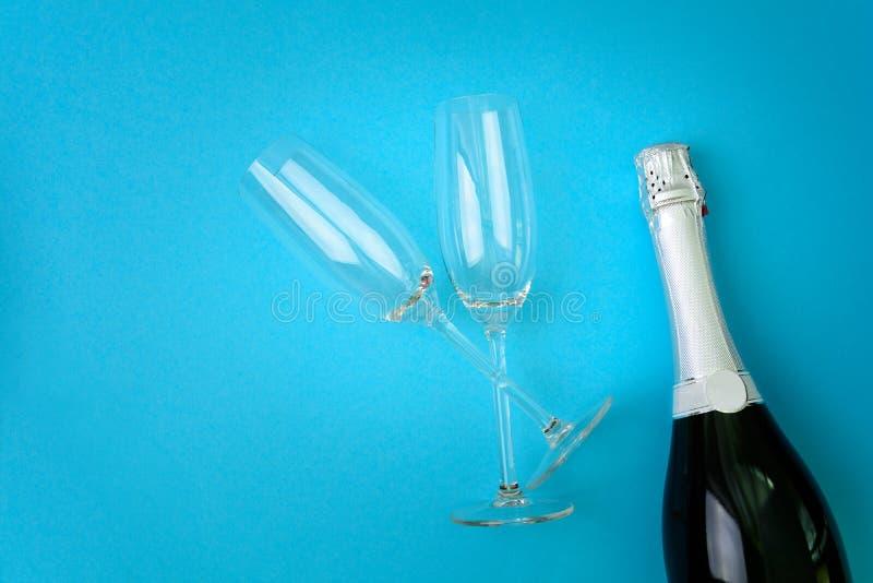 Wijnglazen en fles champagne die op blauwe document achtergrond liggen Het nieuwe concept van de jaarviering royalty-vrije stock foto