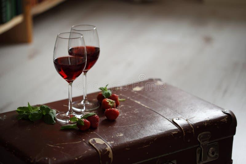 Wijnglazen met rode wijn die met aardbei en munt wordt verfraaid stock foto