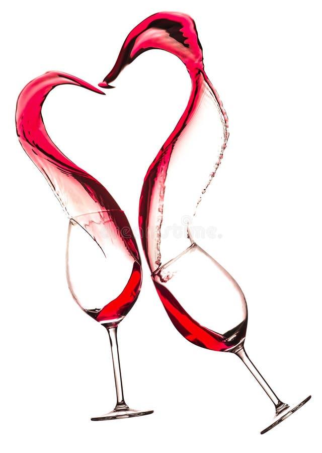 Wijnglazen met rode wijn en hart gestalte gegeven die plons, op wit wordt geïsoleerd stock fotografie
