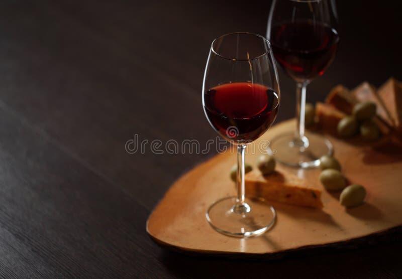 Wijnglazen met rode wijn op hout met kaas en groene olijven - met ruimte voor tekst royalty-vrije stock afbeelding