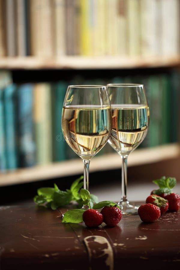 Wijnglazen met witte wijn die met aardbei en munt wordt verfraaid royalty-vrije stock afbeeldingen