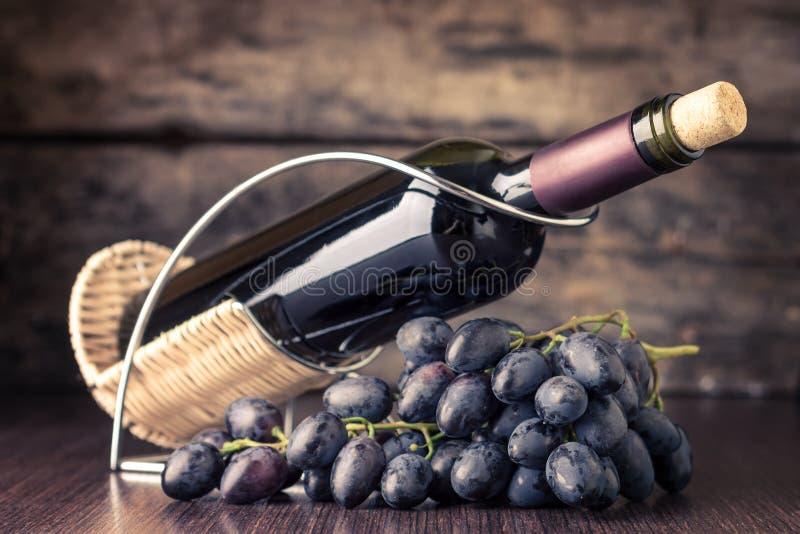 Wijnmakerijachtergrond Fles rode wijn met cluster van donkerblauwe druiven op houten lijst royalty-vrije stock afbeeldingen