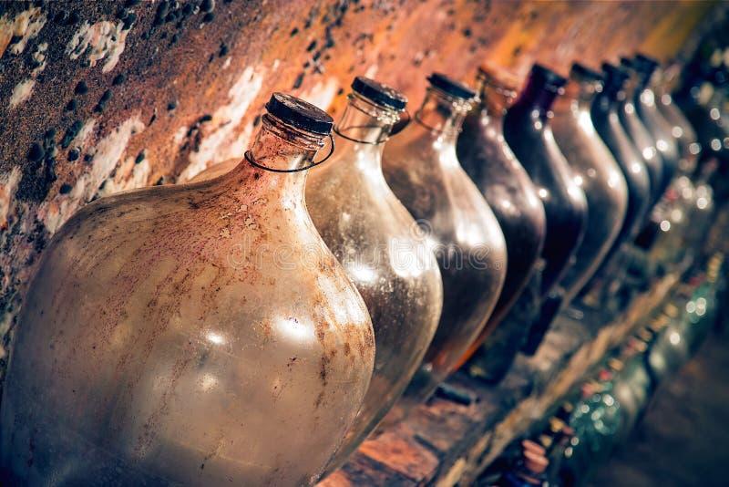 Wijnmandeflessen in de wijnkelder stock foto