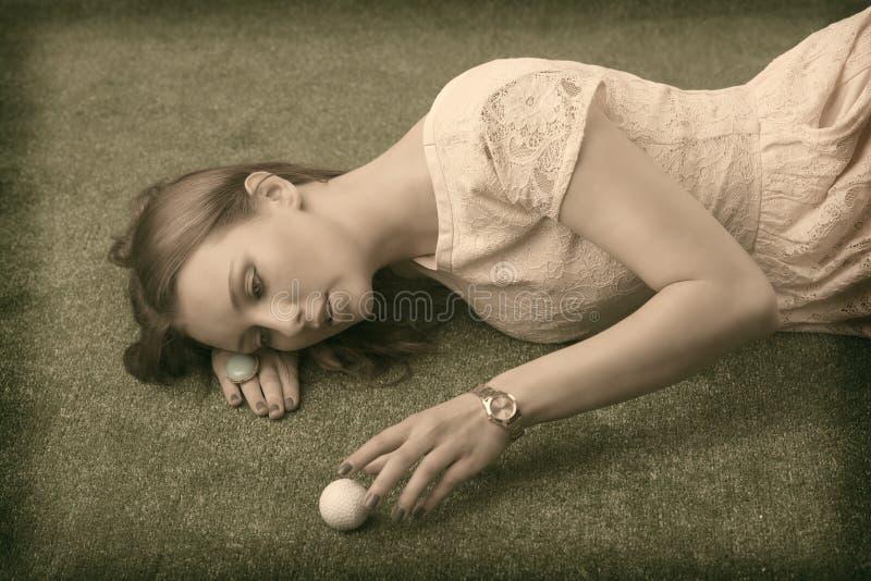 Wijnoogst die girlâs op gras met golfbal ligt royalty-vrije stock afbeeldingen