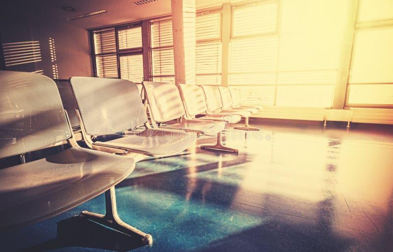 Wijnoogst gefiltreerd beeld van lege luchthavenwachtkamer bij sunris stock afbeelding