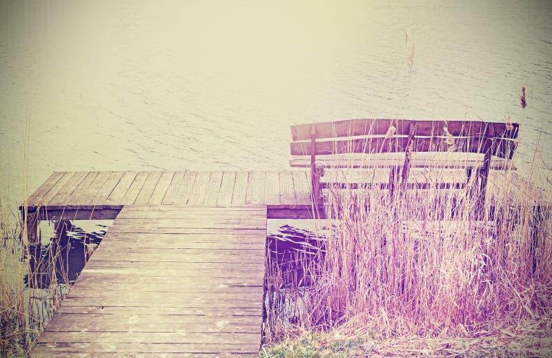 Wijnoogst gestileerde foto van een houten bank bij het meer stock fotografie