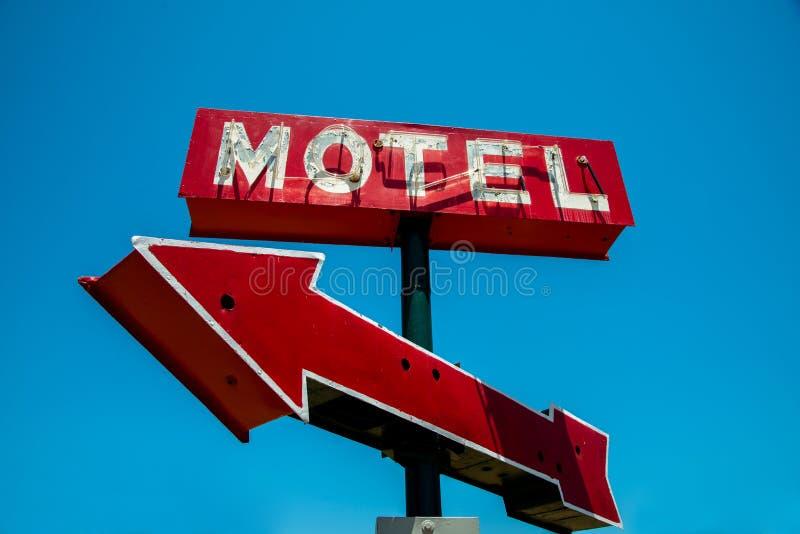 Wijnoogst, neon, rood hotelteken met een rode pijl stock fotografie