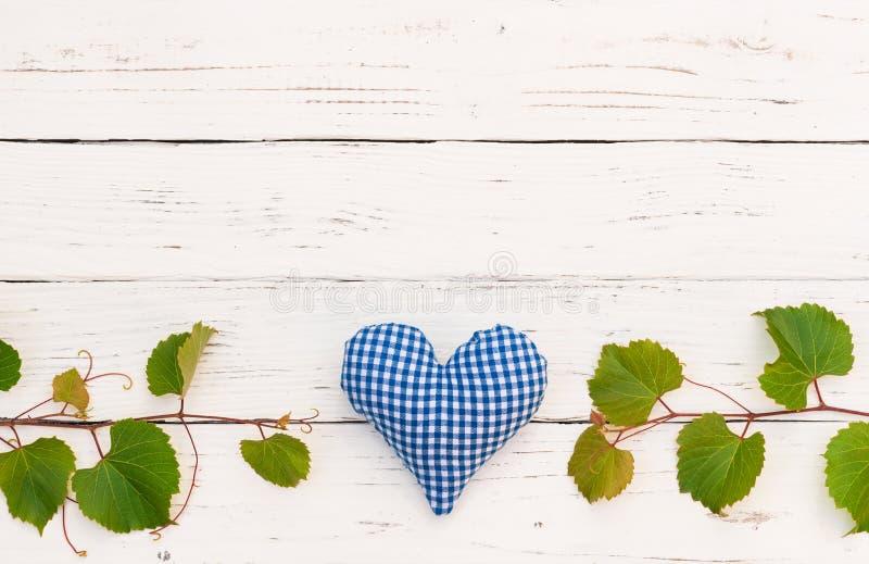Wijnstokachtergrond met wijnstokgrens en blauwe hartdecoratie op witte houten lijst stock afbeeldingen