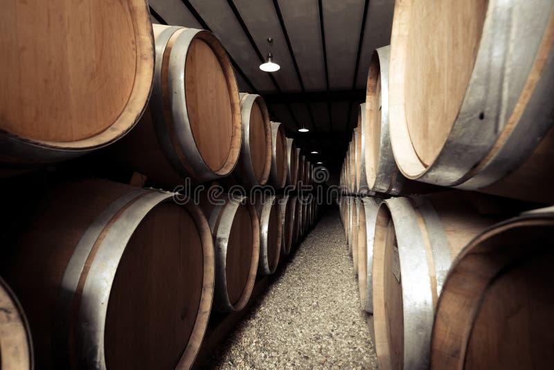 Wijnvatten in oude wijnmakerijkelder die worden gestapeld Uitstekend retro effect stock foto