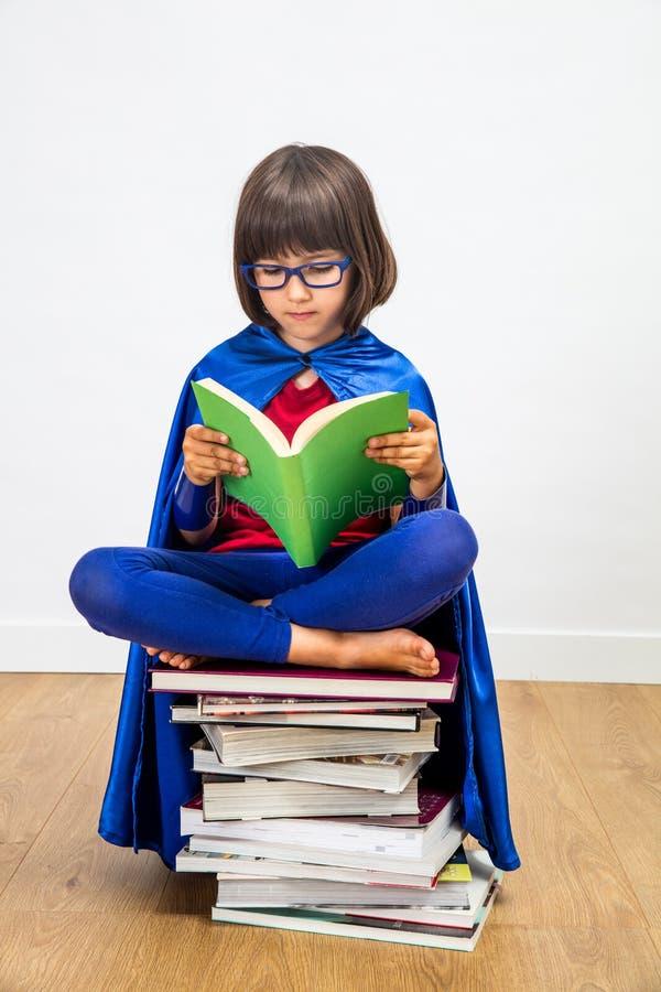 Wijs schoolmeisje met de super lezing van het heldenkostuum voor meisjesmacht royalty-vrije stock afbeeldingen