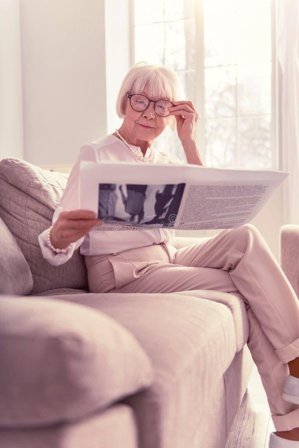 Wijze dame die aandachtig een verse krant lezen stock foto's