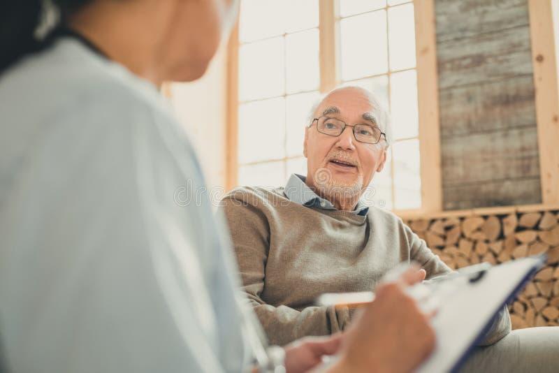 Wijze oude mens die comfortabel gesprek met verpleegster hebben royalty-vrije stock fotografie