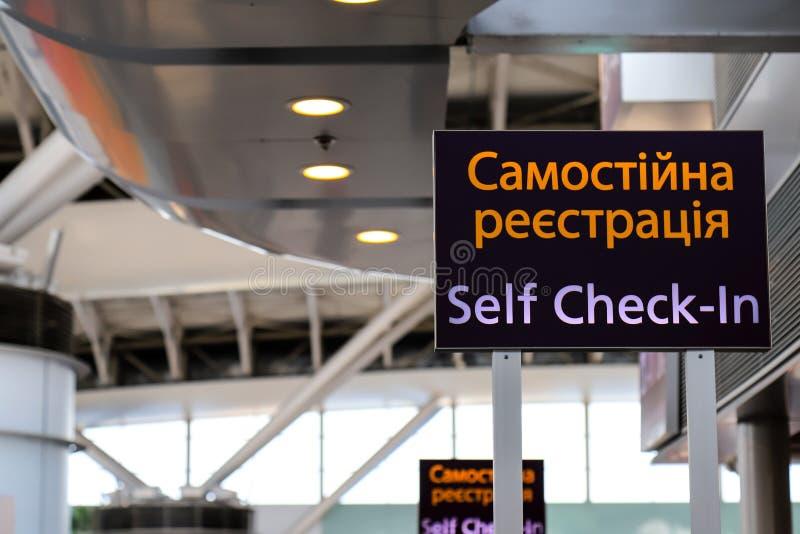 Wijzer met een inschrijving in de Oekraïener - Zelf - controle - binnen bij de luchthaven Informatietribune, zelfregistratiepanee stock afbeelding