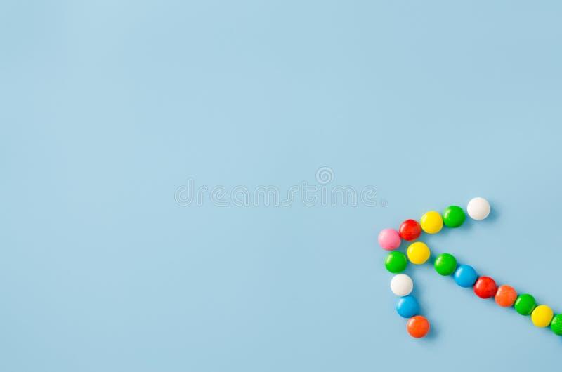 Wijzerpijl van chocoladesuikergoed met gekleurde glans op een blauwe achtergrond stock afbeelding