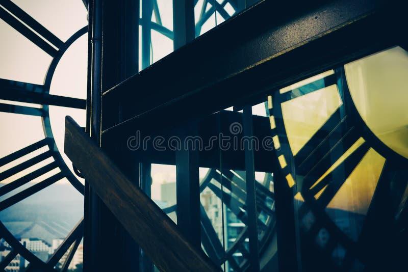 Wijzerplaatbezinning in glas boven stad Blauw en geel Zonsondergang Architecturale achtergrond royalty-vrije stock afbeelding