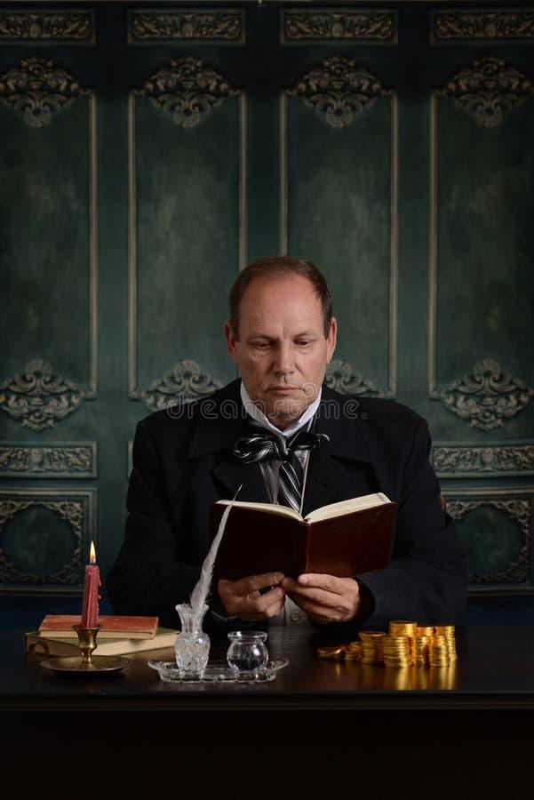 Wiktoriański biznesowego mężczyzna czytanie jest pieniądze księgą główną fotografia stock