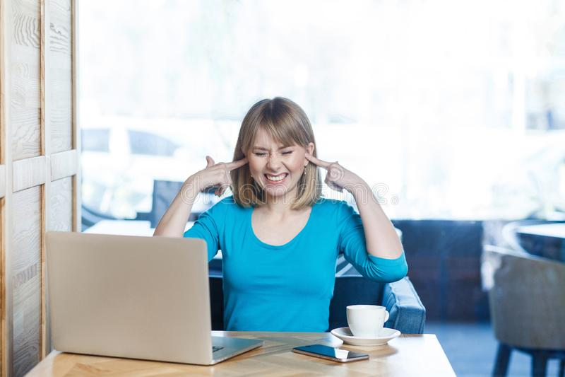 Wil niet horen! Het portret van aantrekkelijk interessant jong meisje freelancer in blauwe blouse zit in koffie en maakt video stock afbeeldingen