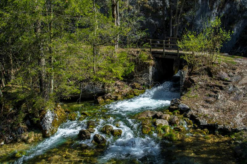 Wild Alpine River With Waterfall And Bridge In Austria stock image