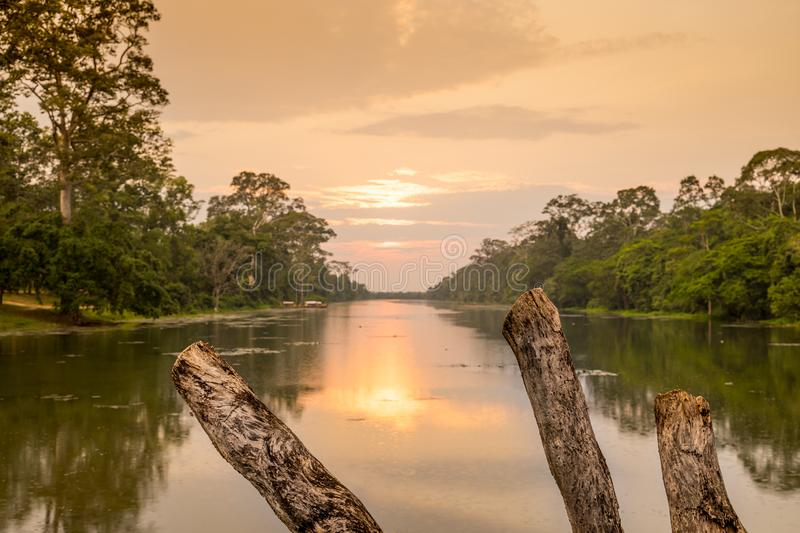 Wild angle shot of sunset above river at angkor wat temple area. Giand starus in the forceground royalty free stock images